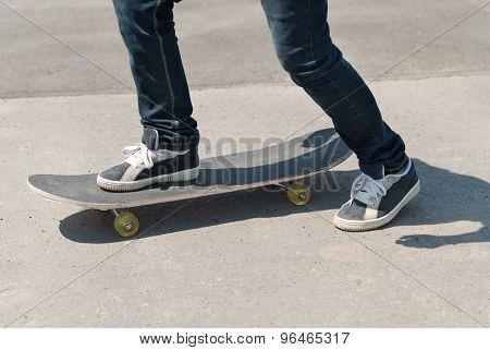 Skateboarder Riding A Skateboard On Asphalt.