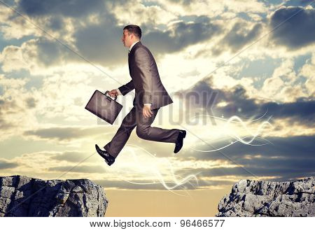 Businessman jumping over abyss
