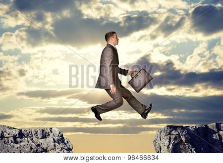 Businessman hopping over abyss