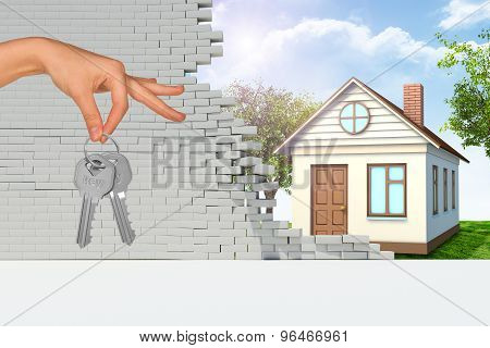 House in broken wall with hand holding keys