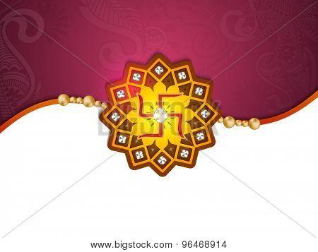 Beautiful shiny rakhi on purple and white background for Indian festival, Raksha Bandhan celebration.