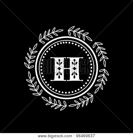 Creative monogram design with English Alphabet H in a floral decorated rounded frame on black background.