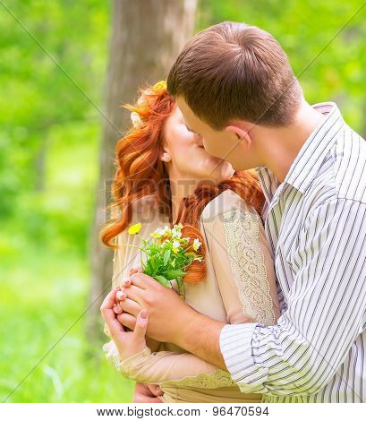 Happy young loving couple kissing outdoors, girl receive a bouquet of flowers from her boyfriend, first affection, romantic relationship
