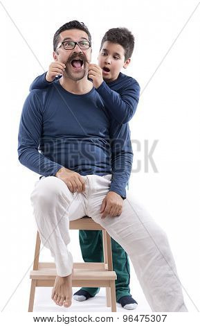 Cute boy surprised to see his father's mustache isolated on white background.