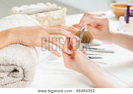 poster of Closeup shot of a woman in a nail salon receiving a manicure by a beautician with nail file. Woman g