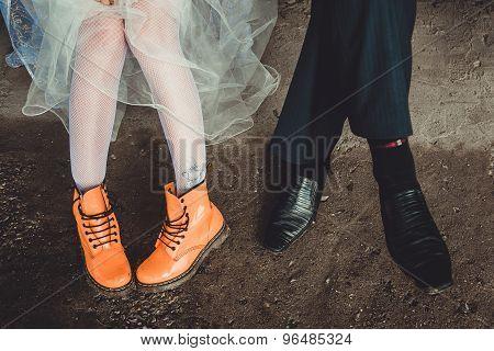 Orange And Black Boots On Legs.