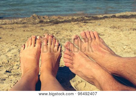 Female and male feet on the background of blue sea. couple lying and resting on the beach.