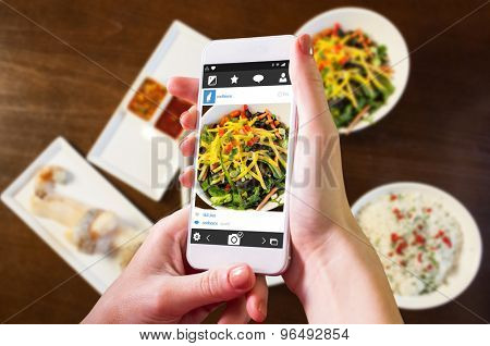 Hand holding smartphone against components of cook it yourself fish dish with hot stone