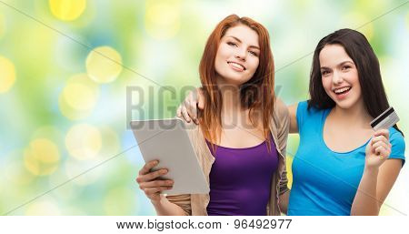 online shopping, e-money, commerce, people and technology concept - two smiling teenage girls or young women with tablet pc computer and credit card over green lights background