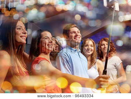 party, technology, nightlife and people concept - smiling friends with smartphone and monopod taking selfie in night club with holidays lights