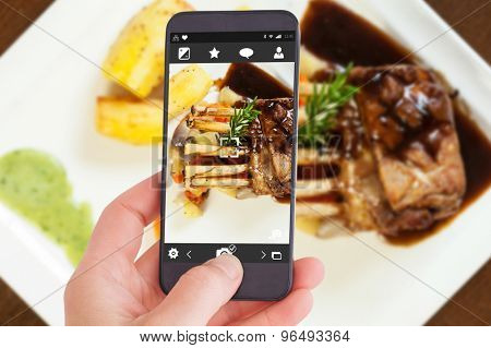 Female hand holding a smartphone against delicious rack of lamb dish with roast vegetable and potatoes