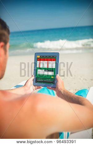 Man using digital tablet on deck chair at the beach against gambling app