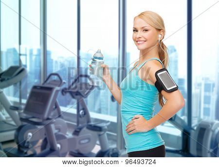 sport, fitness, technology and people concept -- smiling sporty woman with smartphone and earphones listening to music and drinking water over gym machines background