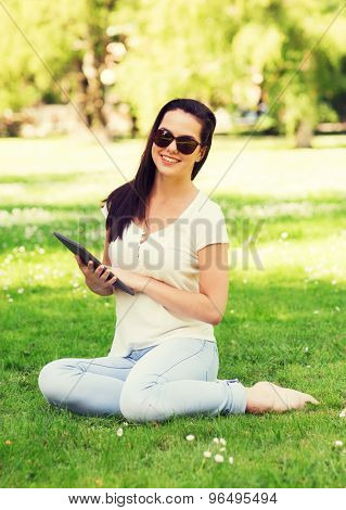 lifestyle, summer, vacation, technology and people concept - smiling young girl with tablet pc sitting on grass in park