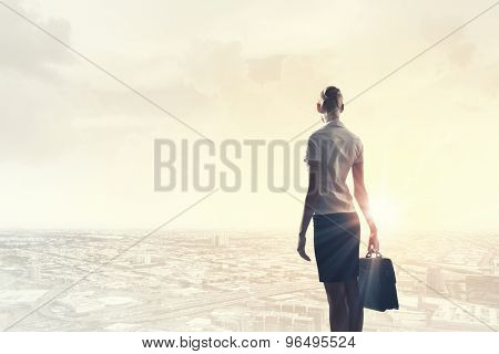 Rear view of businesswoman looking at sunset above city