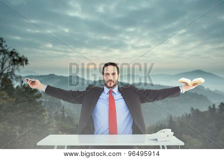 Unsmiling businessman sitting with arms outstretched against trees and mountain range against cloudy sky