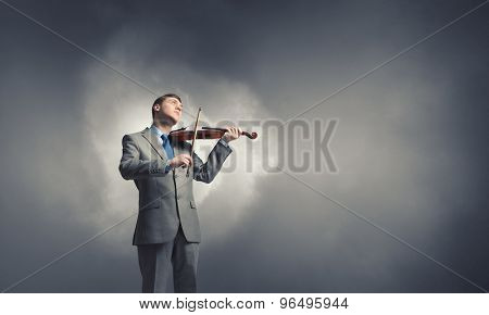 Young smiling businessman in suit playing violin