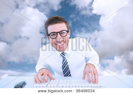 Businessman working at his desk against blue sky with white clouds