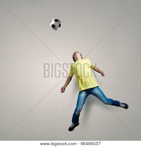 Man in casual kick football ball over head