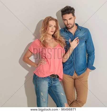 Side view of a young blonde woman holding her hand on her waist while her lover is holding his hands in pockets.