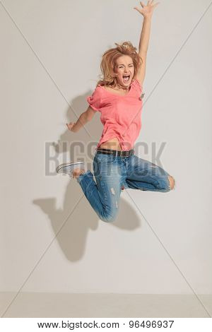 Screaming woman jumping with her hands in the air on grey studio background.