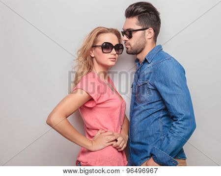 Side view of a young casual man looking at his girlfriend while she is holding her hands on her waist.