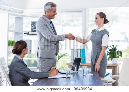 Business people shake hands during interview in office