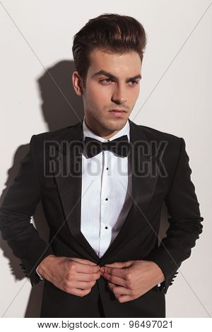 Handsome young fashion man looking away from the camera while unbuttoning his jacket.