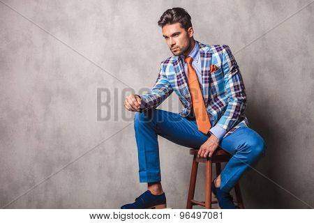 Side view picture of a young business man sitting on a chair while resting his leg on a wood box.