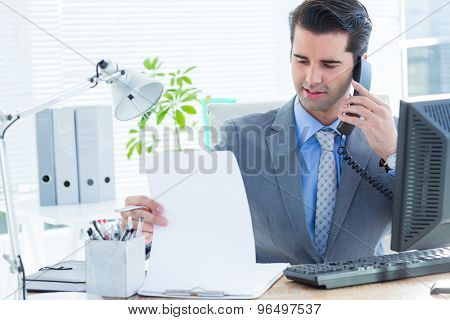 Professional businessman checking at his notebook while on the phone