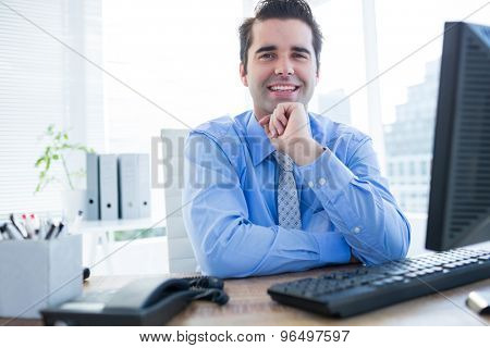 Cheerful young businessman using computer in the office