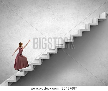 Young woman in evening long dress walking up the staircase