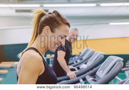 Fitness woman laughing with friend in treadmill training