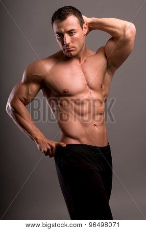 handsome young bodybuilder showing of his fit body