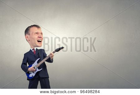 Young businessman in suit with big head playing guitar