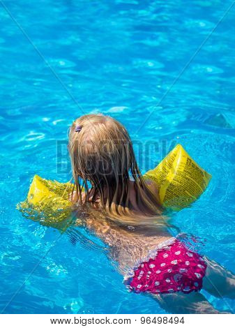 Little girl swimming in the swimming pool