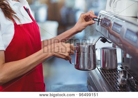 A barista using the coffee machine at the cafe