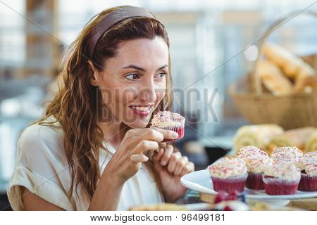 Pretty brunette holding and smelling cupcake in the bakery store