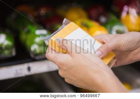A pretty blonde woman buying some cheddar in the supermarket