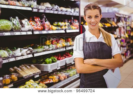 Pretty blonde looking at camera with arms crossed in supermarket