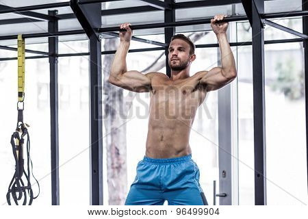 Front view of a muscular man doing pull up exercises