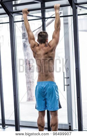 Back view of a muscular man doing pull up exercises