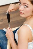 stock photo of enthusiastic  - Woman assembling wooden furniture using screwdriver - JPG