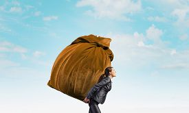picture of heavy bag  - Businesswoman carrying big heavy bag on back - JPG