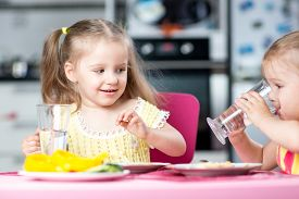 pic of daycare  - Cute little children drinking water at daycare or nursery - JPG