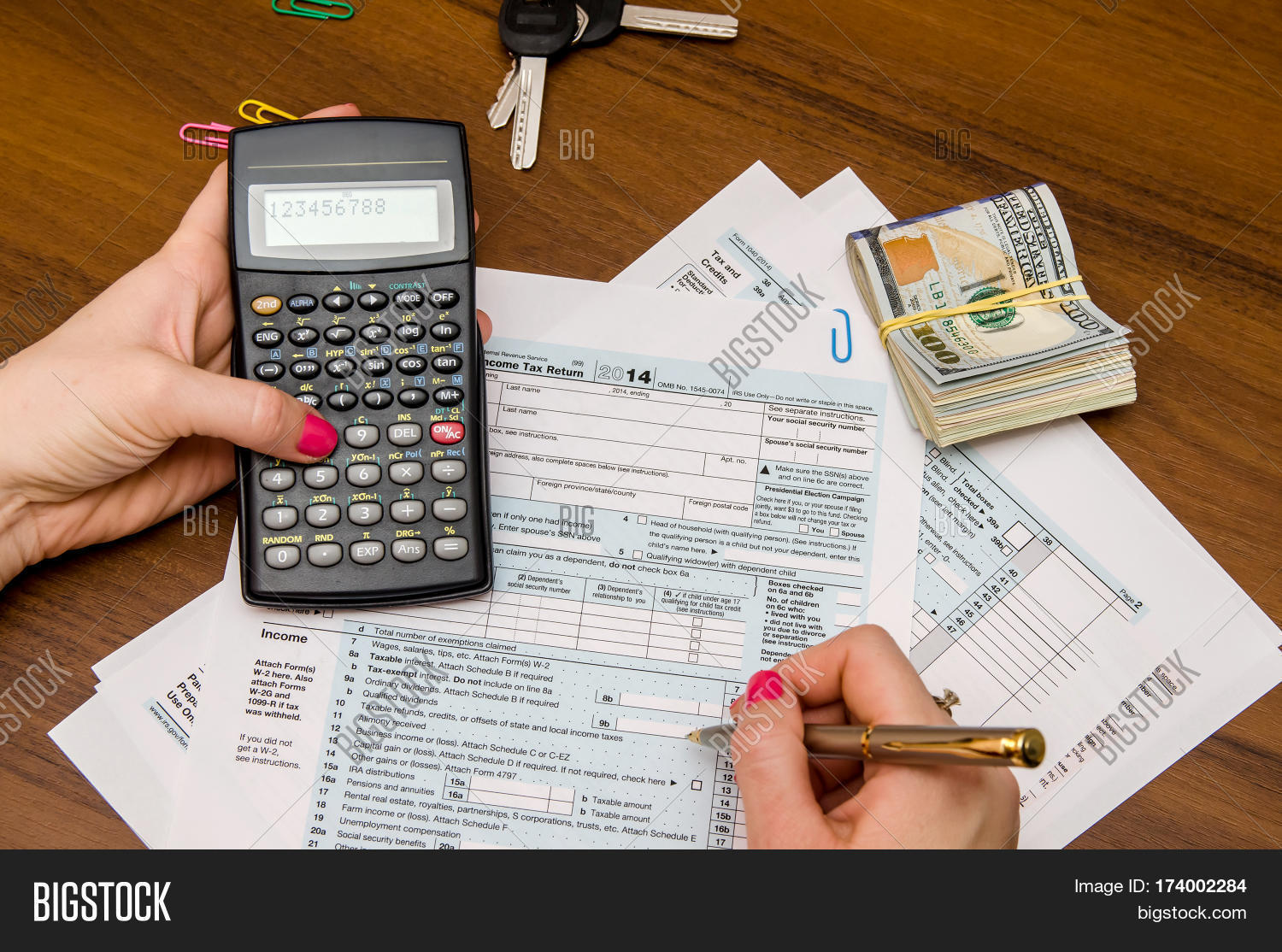 Taxpayer filling out 1040 tax form with pen and calculator for 1040 tax table calculator