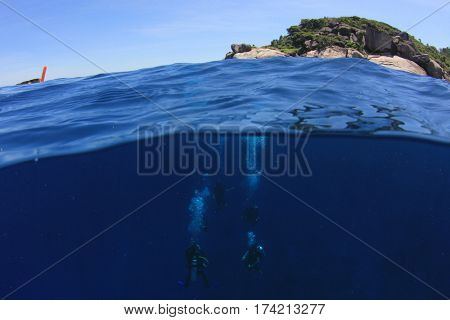 Scuba diving underwater. Over under half and half split photo. Ocean, surface, sky and island