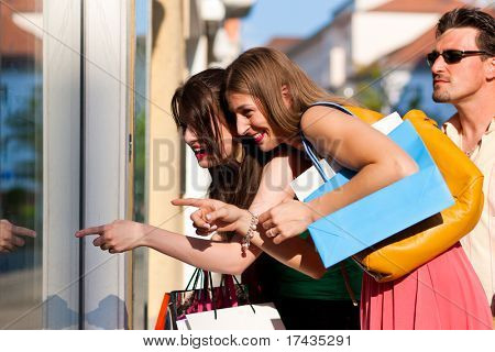 Two women being friends shopping downtown with colorful shopping bags, they are lolling into a glass store door and are amazed; in the background a man is standing