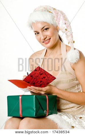 A young sexy woman in santarina outfit with christmas card
