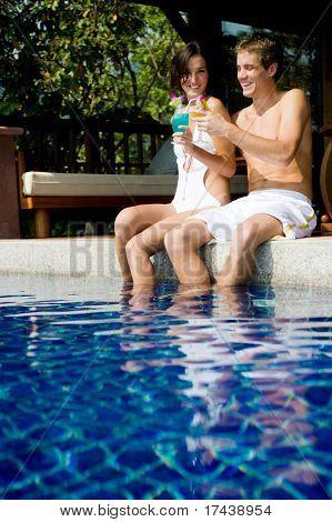 Una piscina de joven atractiva pareja sentada con cócteles tropicales
